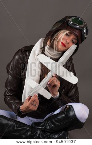 woman in aviator hat sitting with toy airplane in hands
