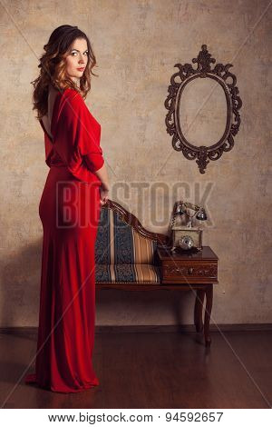 Girl Wearing A Red Dress Standing In Retro Room