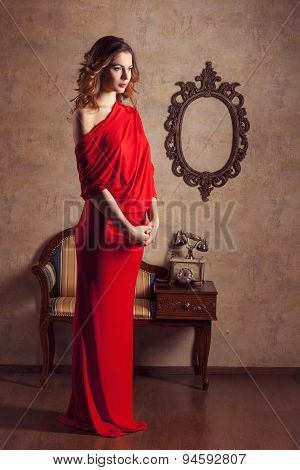 Beautiful Girl In Red Dress Standing And Looking Down