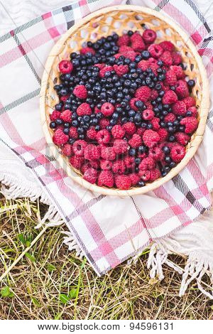 Raspberries and blueberries in a basket on a tablecloth for a picnic