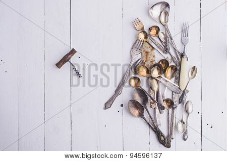 Forks, spoons, old-style corkscrew on white table