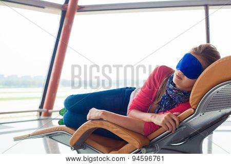 woman relaxing in eye sleep mask at airport terminal awaiting the flight