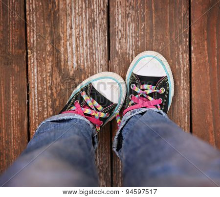 a wide angle photo of a pair of generic looking shoes like converse sneakers with pink shoe laces on a vintage wooden background making a emotion gesture by pointing one foot in