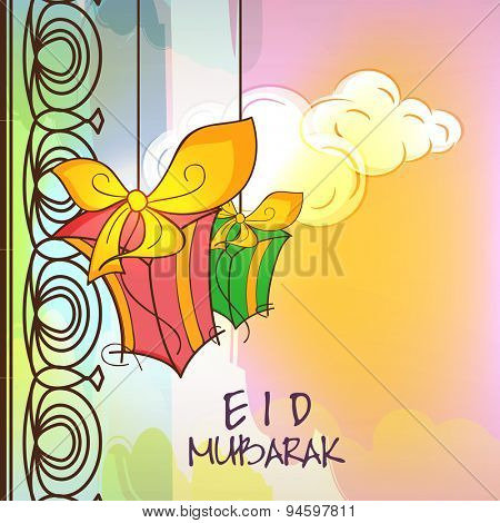 Elegant greeting card design with hanging gift boxes on cloudy colorful background for Muslim community festival, Eid celebration.