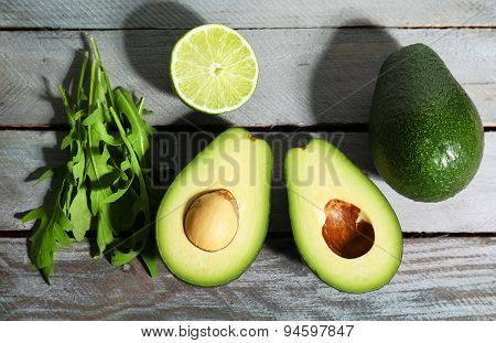 Sliced avocado, arugula on wooden background