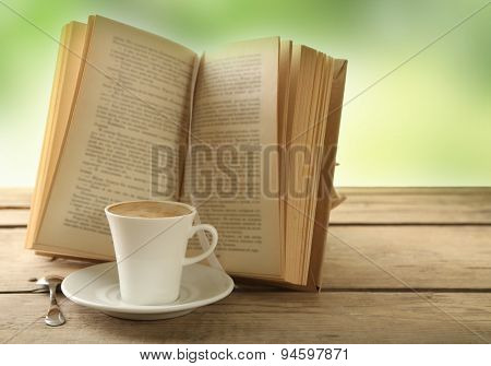 Cup of coffee and book on wooden table, on green background