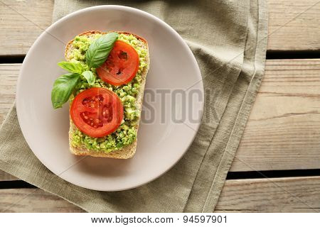 Vegan sandwich with avocado and vegetables on plate, on wooden background