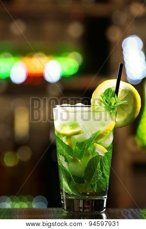 Glass of cocktail in bar on bright blurred background