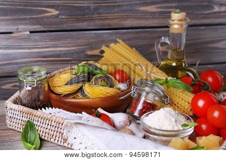 Pasta with cherry tomatoes and other ingredients on wooden planks background