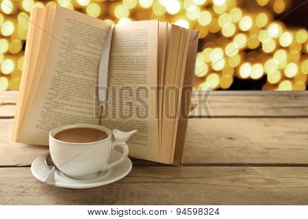 Cup of coffee with open book on bright background