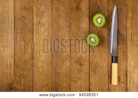 Halves of kiwi with knife on wooden background