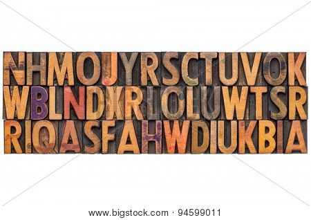background of vintage letterpress wood type printing blocks, random letters of alphabet stained by color inks, isolated on white