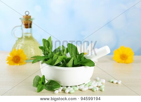 Herbs, berries, flowers and pills on color  wooden table, on bright background
