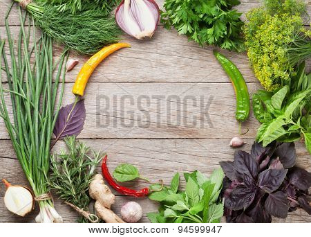 Fresh garden herbs and spices over wooden table. Top view with copy space