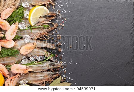 Fresh prawns with spices on black stone background. Top view with copy space