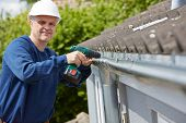 picture of gutter  - Workman Replacing Guttering On Exterior Of House - JPG