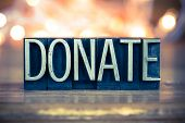pic of tithe  - The word DONATE written in vintage metal letterpress type on a soft backlit background - JPG