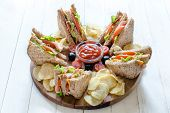 foto of potato chips  - Large group of clup sandwiches with potato chips and ketchupselective focus - JPG