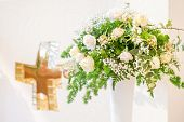 foto of purity  - A wedding bouquet of white flowers in front of the white altar with a golden cross - JPG
