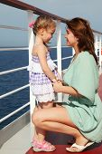 Mother Sitting Near Daughter And Holding Her For Hand On Cruise Liner Deck, Side View, Sunny Day
