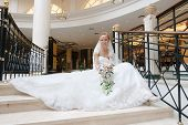 Bride in beautiful wedding dress sits on wide spiral staircase with bunch