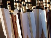 image of fletching  - close up view of a stack of handmade arrows showing feathers and binding - JPG