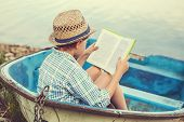foto of old boat  - Boy reading the book in the old boat - JPG