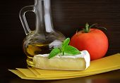 stock photo of brie cheese  - cheese brie and olive oil on a dark background - JPG