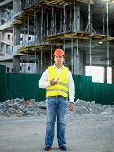 image of scaffold  - Engineer in helmet on construction site posing against scaffolding - JPG
