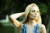 stock photo of natural blonde  - Portrait of thoughtful pretty blond woman outdoor in summer daylight on natural background horizontal picture - JPG