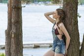 picture of jetties  - woman with relaxed expression wearing bikini under overalls and braid hair - JPG