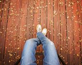 stock photo of loafers  - a pair of legs taken from overhead on a deck with leaves that have fallen  - JPG