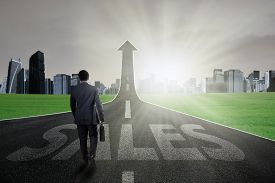 picture of going out business sale  - Young manager walking on the road with a sales text and going up as an arrow - JPG