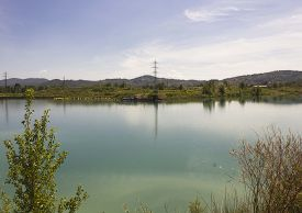 image of paysage  - Peaceful lake inside Renai Park in Signa near Florence with cloud reflected in the water and current poles in the background - JPG