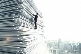 stock photo of climb up  - businessman climbing up a huge stack of paper - JPG