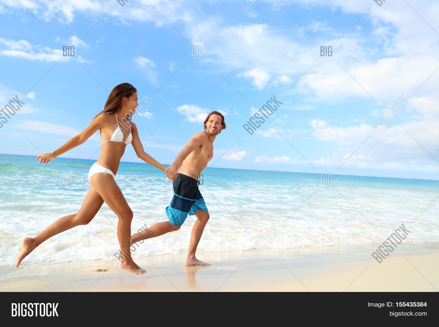 Happy Beach Couple Vacation Getaway Young People In Bikini And Swimwear Running Holding Hands Together