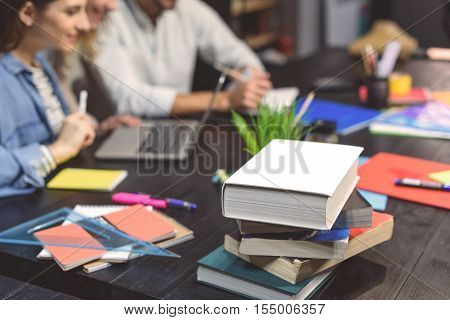 Preparing to exams. Close up photo of books lying on table with students sitting at desk and learning in background