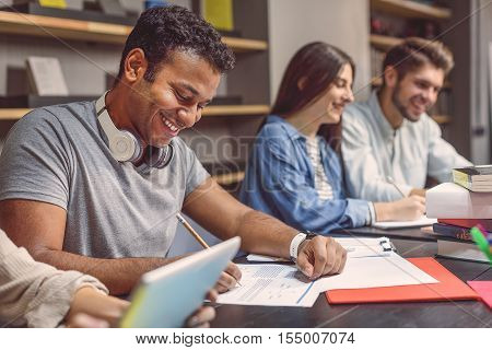 Working on their latest assignment. Smiling African student sitting at desk in library and making notes on files next to his colleagues on study