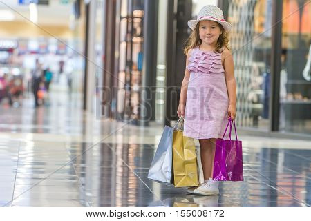 cute little girl in fashionable hat on shopping. portrait of a kid with shopping bags. child in shop