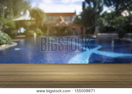 Wooden Board Empty Table Against Of Blurred Swimming Pool Background. Perspective Brown Wood Over Sw