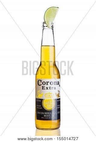 LONDON UNITED KINGDOM - NOVEMBER 04 2016: Bottle of Corona Extra Beer with lime slice.Corona produced by Grupo Modelo with Anheuser Busch InBev is the most popular imported beer in the US.