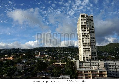 Makiki Roosevelt High School and Tantalus Mountain with houses and modern highrises and other small buildings on a beautiful day on Oahu Hawaii June 2016.