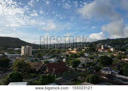 Punchbowl Crater Makiki Roosevelt High School and Honolulu Cityscape looking to the ocean from high up in the hills with houses and modern highrises and other small buildings on a beautiful day June 2016.