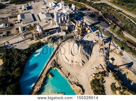 Fossil Fuel Open Pit Mine Extracting Limestone deposits outside of Austin , Texas with large pools of water and piles of minerals