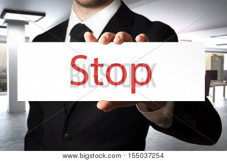 businessman in black suit showing sign stop