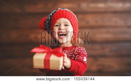 happy child girl with a Christmas present on wooden background