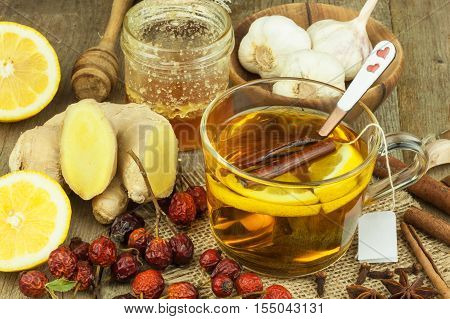 Natural treatment for colds and flu. Ginger lemon honey garlic and rosehip tea against influenza. Hot tea for colds. Home Pharmacy. Proven treatment of diseases. Folk medicine.