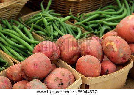 Baskets filled with fresh picked potatoes and beans, a staple at local farmers markets.