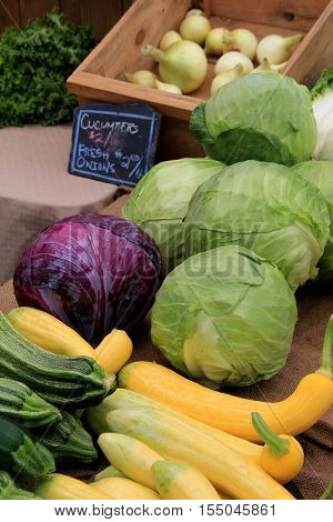 Vertical image of fresh picked vegetables on table at local market
