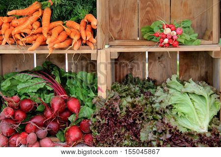 Wood crates filled with fresh crop of vegetables, set on table at farmers market